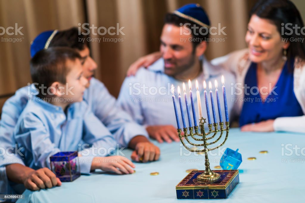 Family of four celebrating hanukkah stock photo