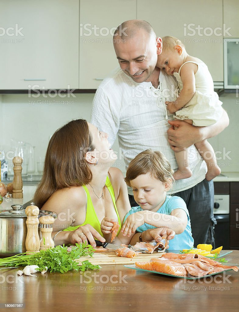 family of four cooking salmon fish at home kitchen royalty-free stock photo