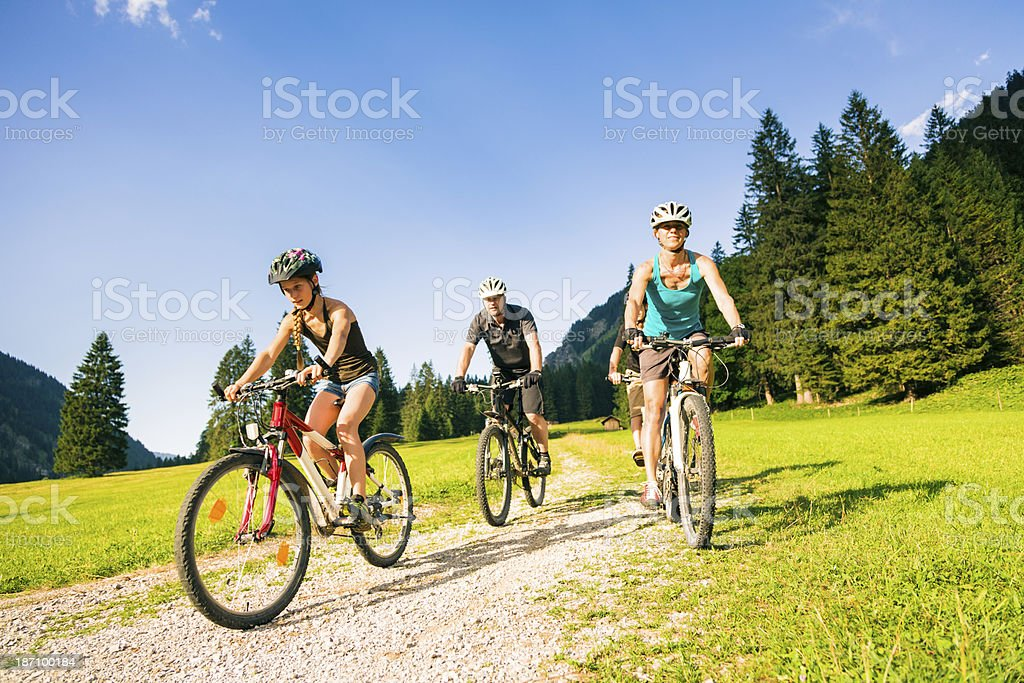 family of four cycling stock photo
