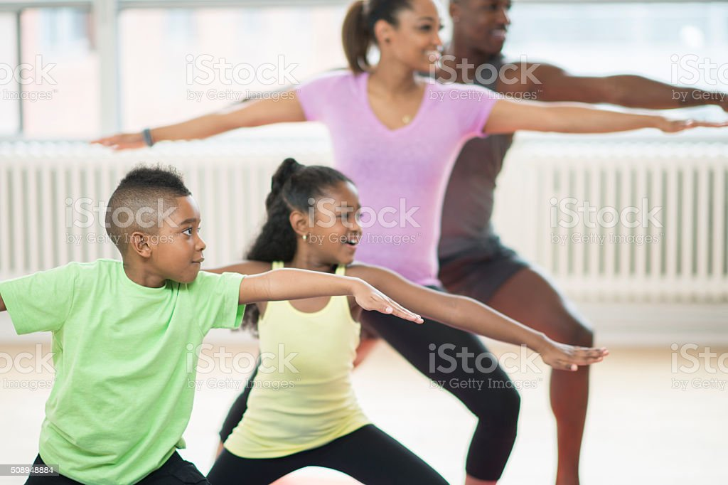 Family of Four Doing Yoga at the Gym stock photo