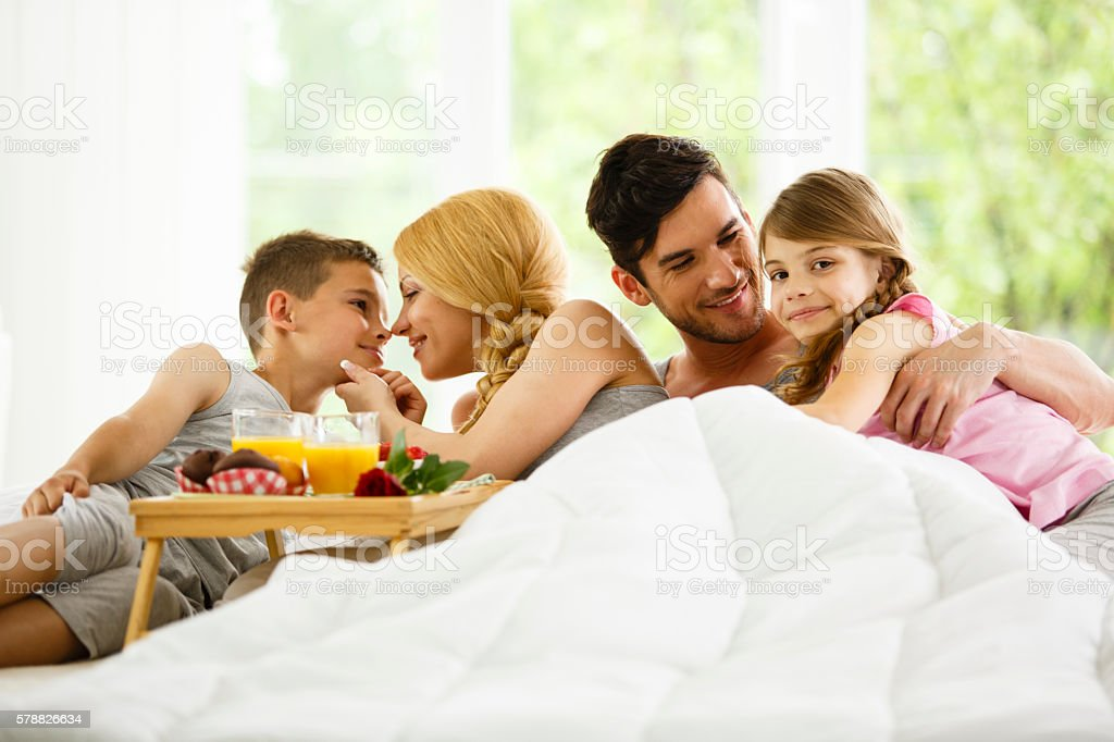 Family of four eating breakfast in bed stock photo