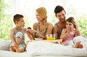 Family of four eating breakfast in bed