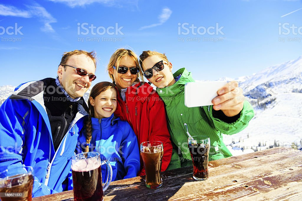 family of four enjoying a drink in the alps royalty-free stock photo