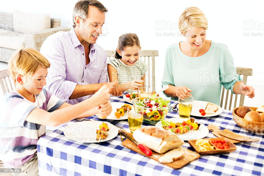 Family Of Four Enjoying Meal Together At Dining Table royalty-free stock photo