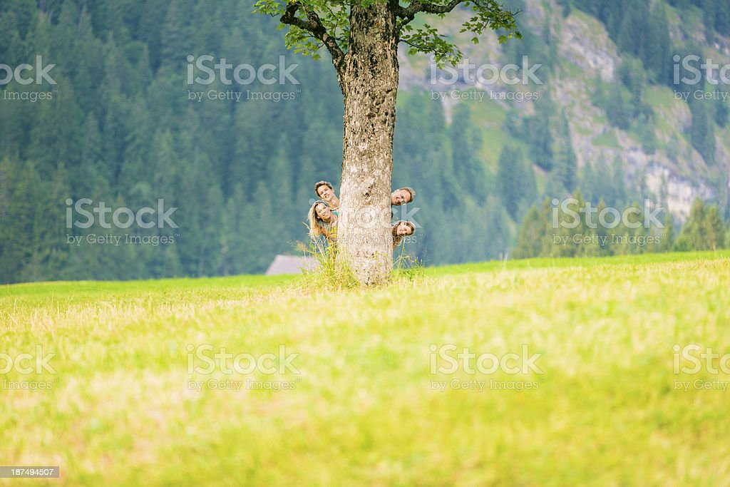family of four hiding behind tree royalty-free stock photo