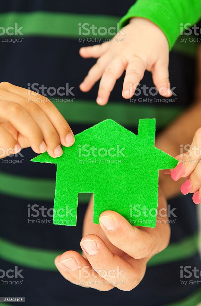 Family of four holding green house in hands stock photo