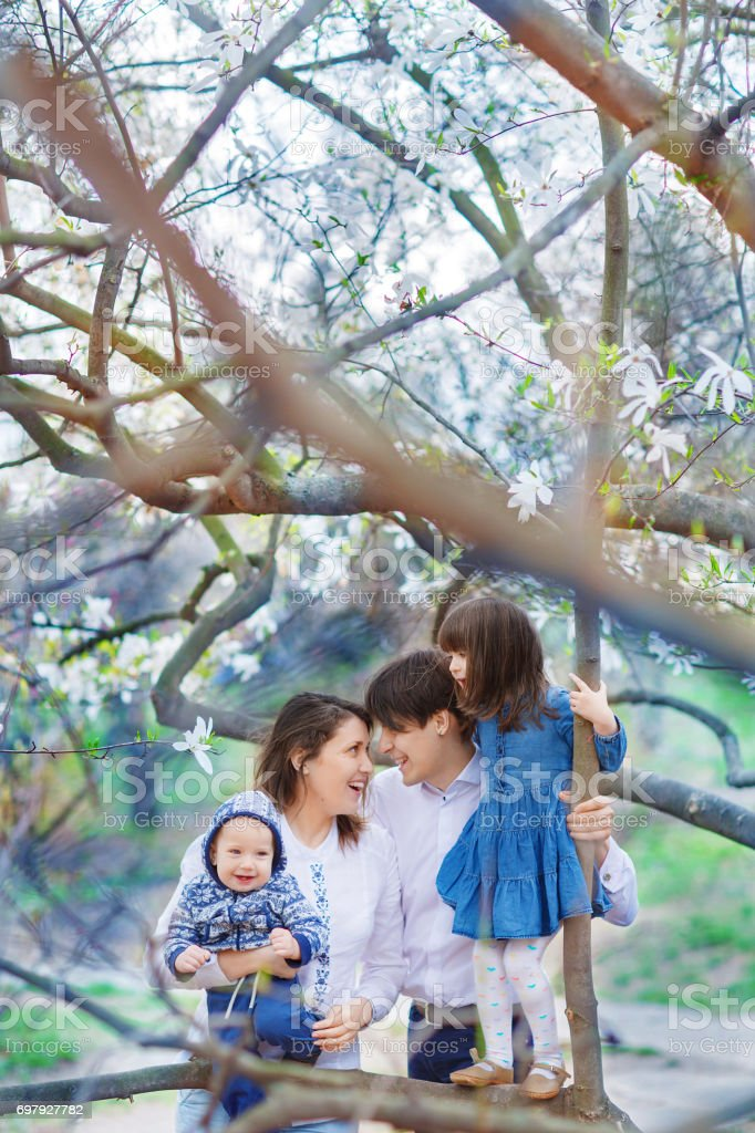 Family of four hugging in the garden with blooming magnolias stock photo