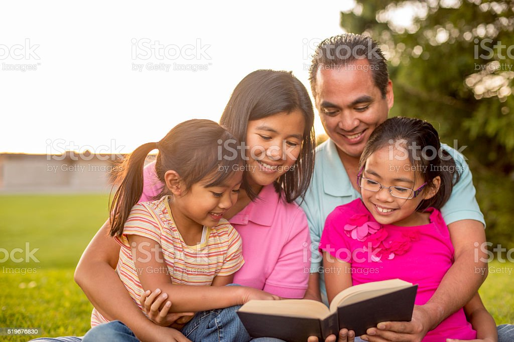 A family of four is hanging out together in the park stock photo