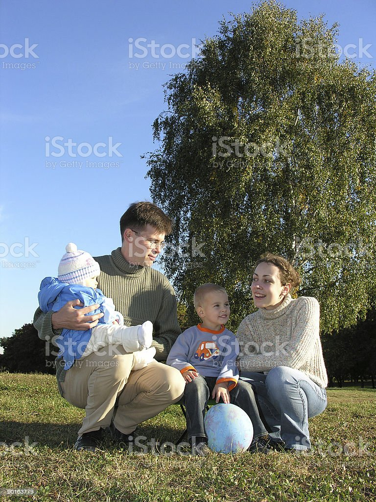 Family of four on grass blue sky autumn stock photo