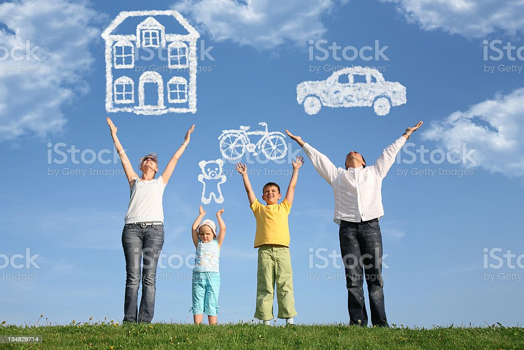 Family of four on grass with hands up and dream stock photo