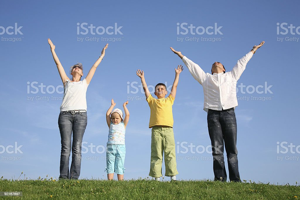 family of four on grass with hands up royalty-free stock photo