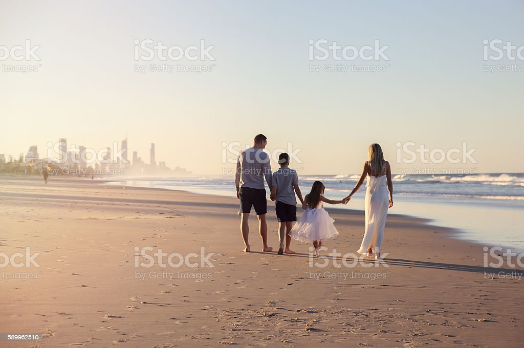 Family of four portrait on the beach, toning soft focus stock photo