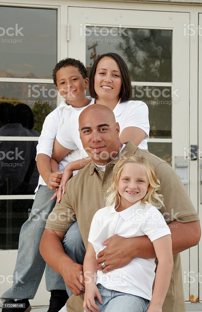 Family of four posing in front of house royalty-free stock photo