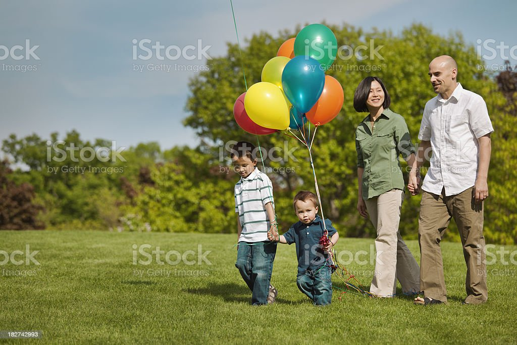 Family of Four Quality Time Walking in Park with Balloons stock photo