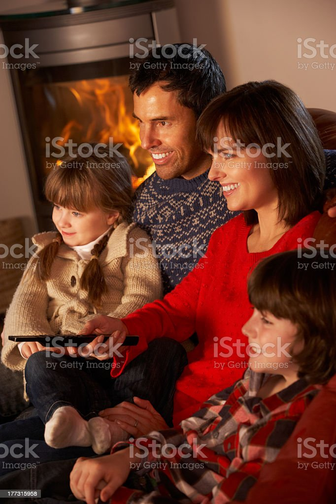 Family of four relaxing by cozy fire while watching tv stock photo