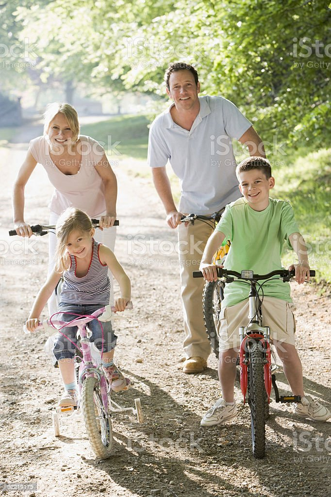 Family of four riding bicycles in a woodland royalty-free stock photo