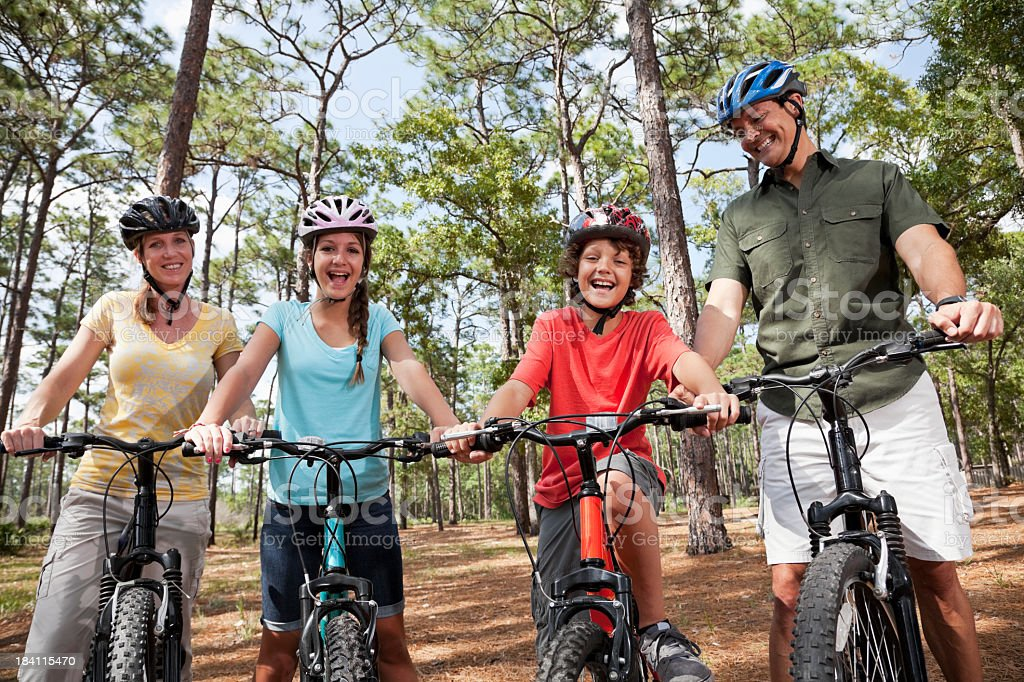 Family of four riding bicycles stock photo