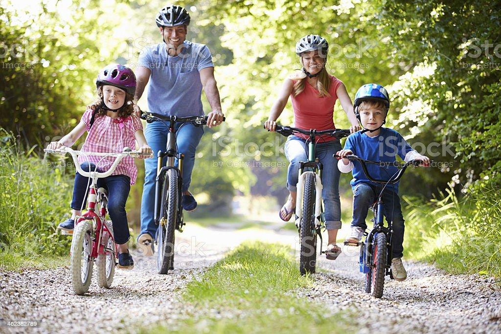 Family of four riding bikes on gravel road royalty-free stock photo