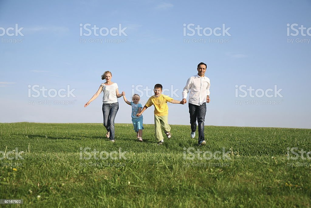 family of four running grass sky royalty-free stock photo