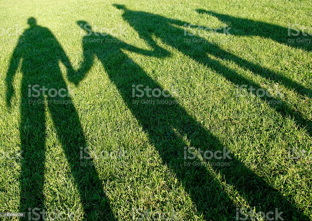 Family of four shadows in the park stock photo