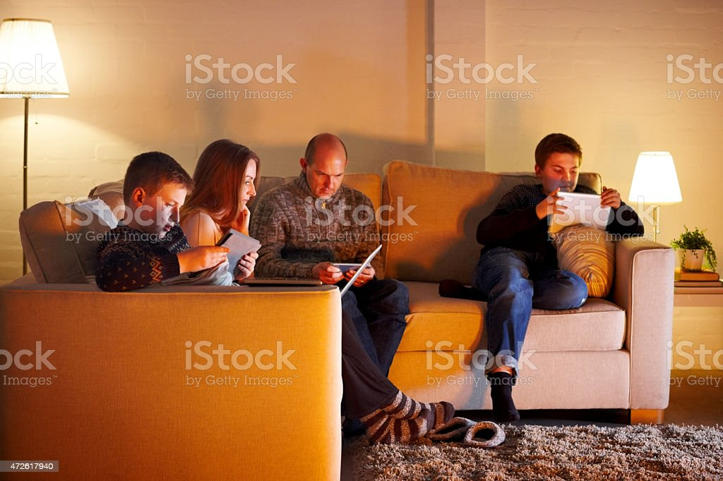 Family of four sitting on couch using digital devices stock photo