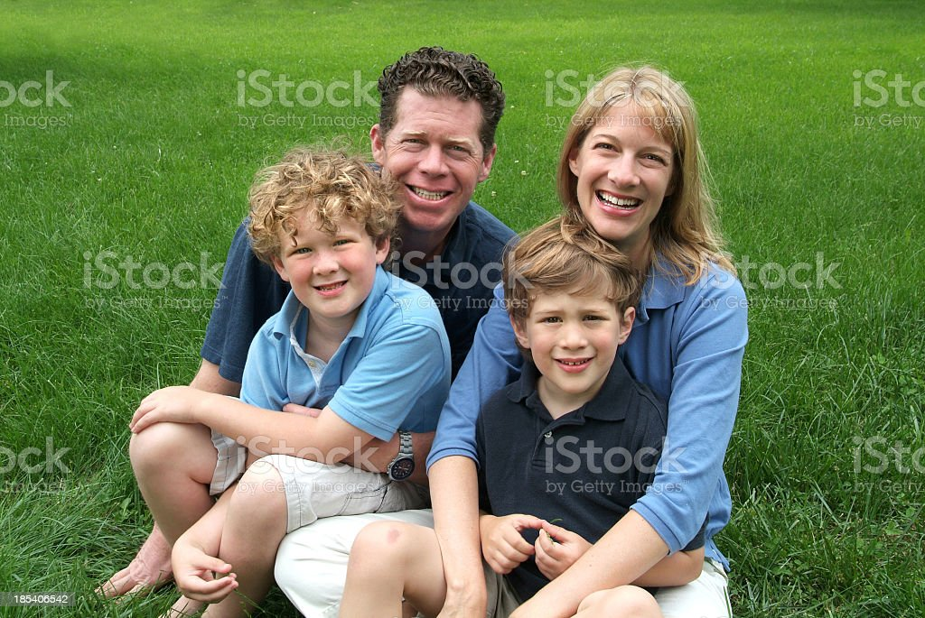 Family of Four Sitting Outside on a Sunny Summer Day royalty-free stock photo