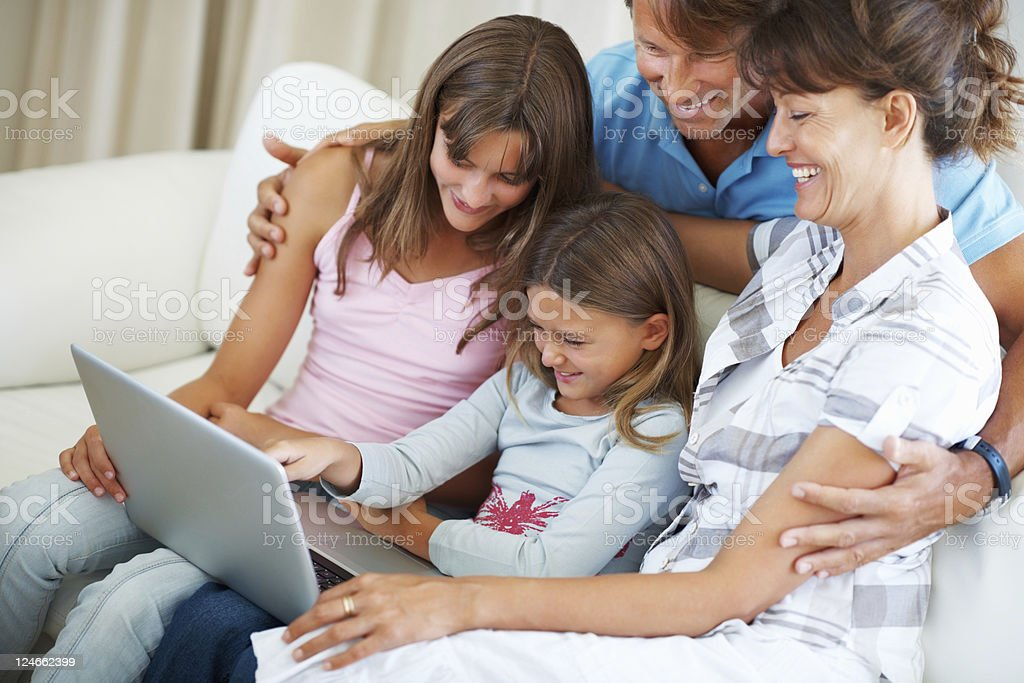 Family of four using laptop and smiling royalty-free stock photo