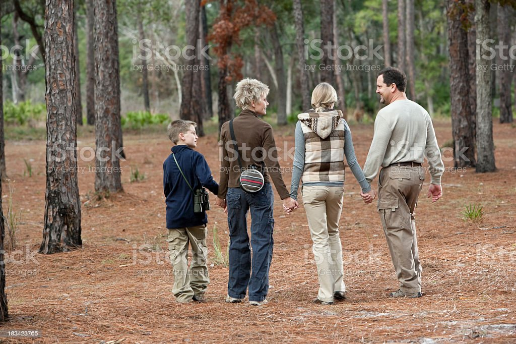Family of four walking together in park royalty-free stock photo