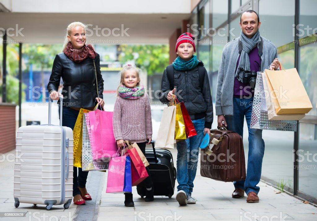 Family of four with shopping bags stock photo