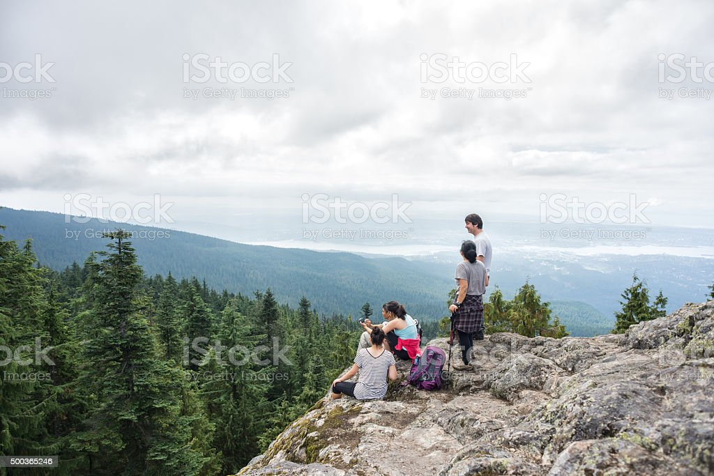 Family of Hikers Rest and Enjoy View on Wilderness Mountaintop stock photo