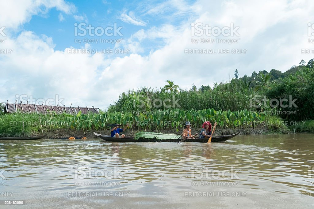 Family of Mentawai tribes crossing the river by tra stock photo