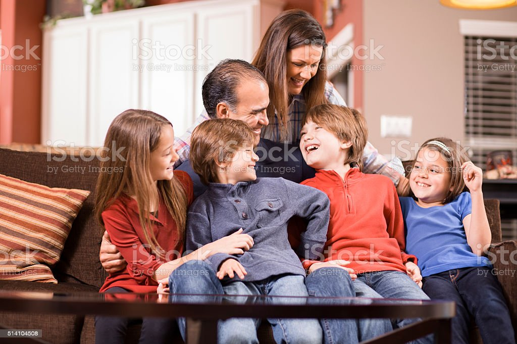 Family of six plays together at home.  Mixed races. stock photo
