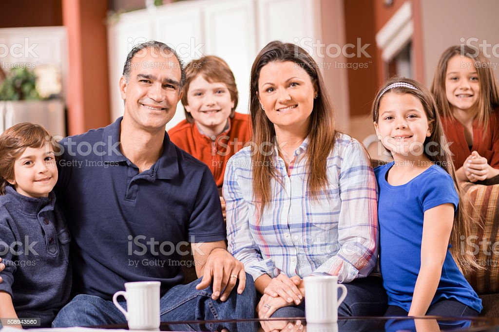 Family of six poses together at home.  Mixed races. stock photo