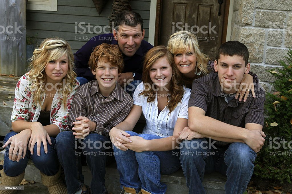 Family of six sitting in front step of their house stock photo