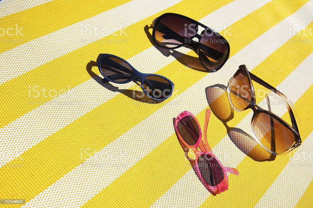 Family of Sunglasses on Bright Striped Yellow Lounge Chair royalty-free stock photo