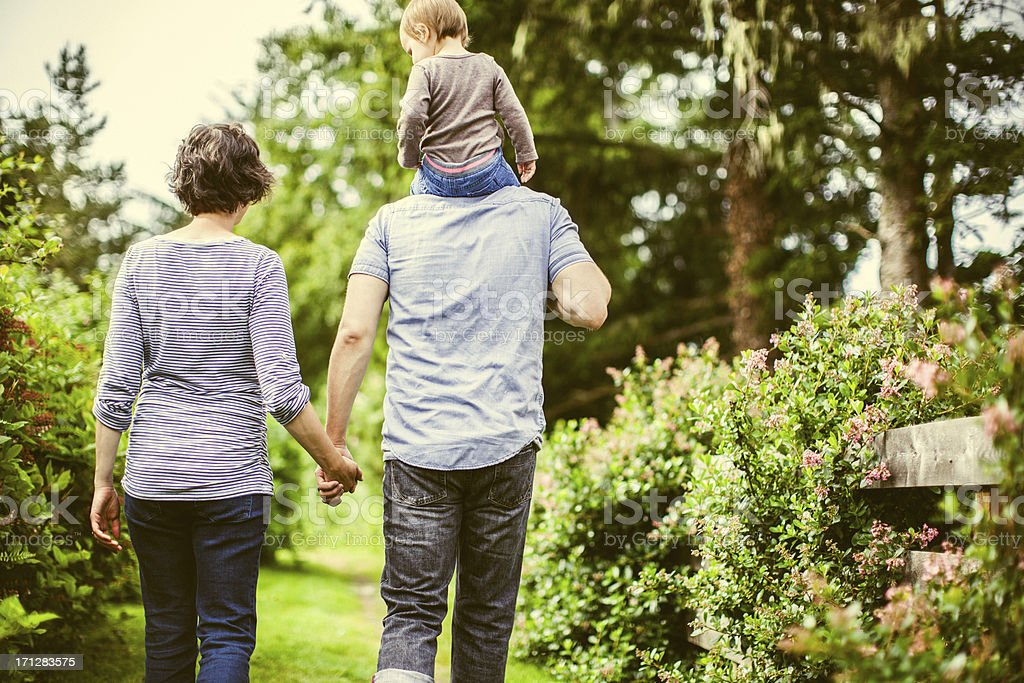 Family of three hiking together in garden stock photo
