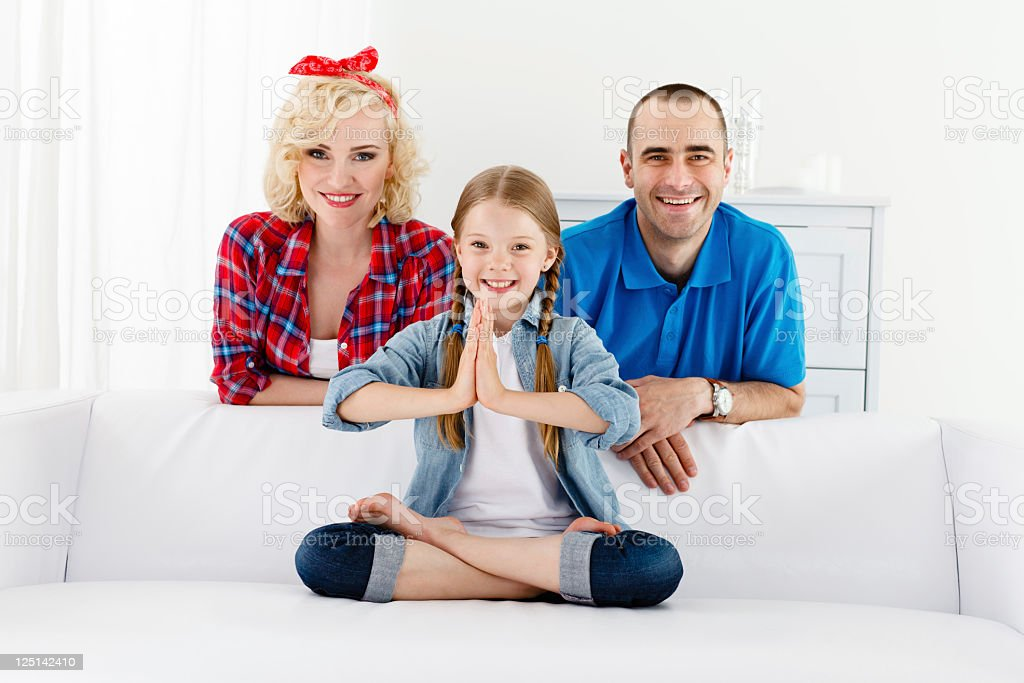 Family of Three on Couch, Daughter Doing Yoga royalty-free stock photo