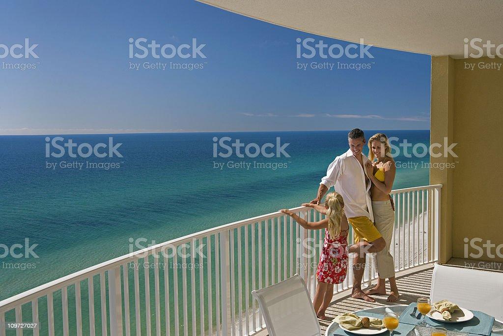 Family of Three On Hotel Balcony Overlooking Ocean stock photo