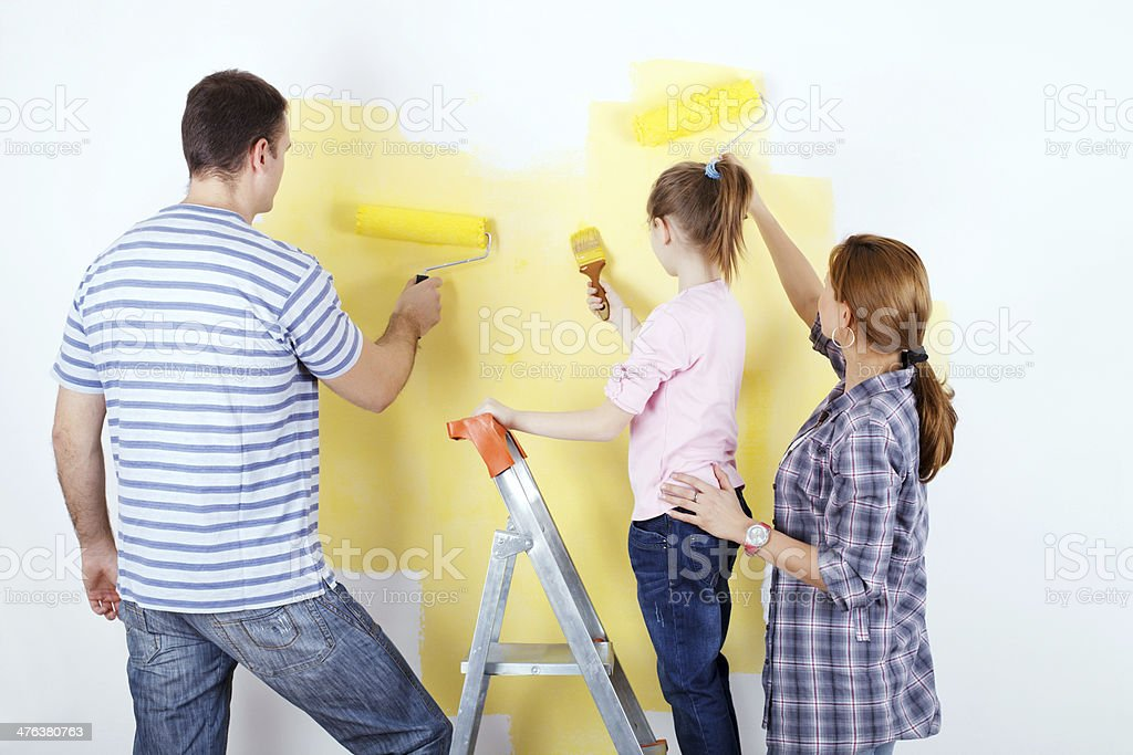 Family of three painting the wall. royalty-free stock photo