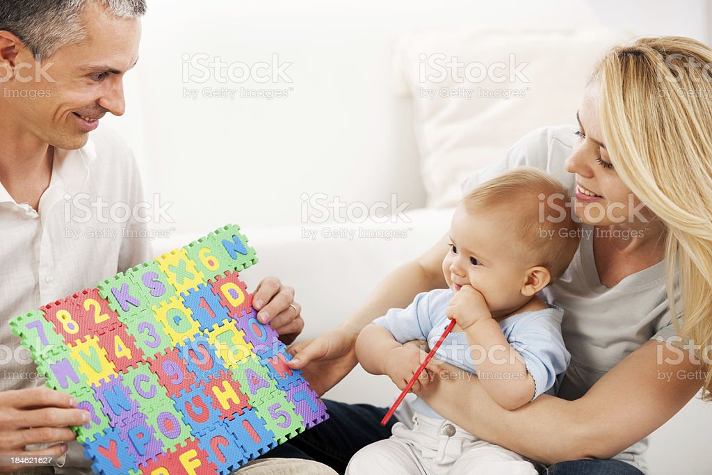 Family of three people playing with puzzles. royalty-free stock photo
