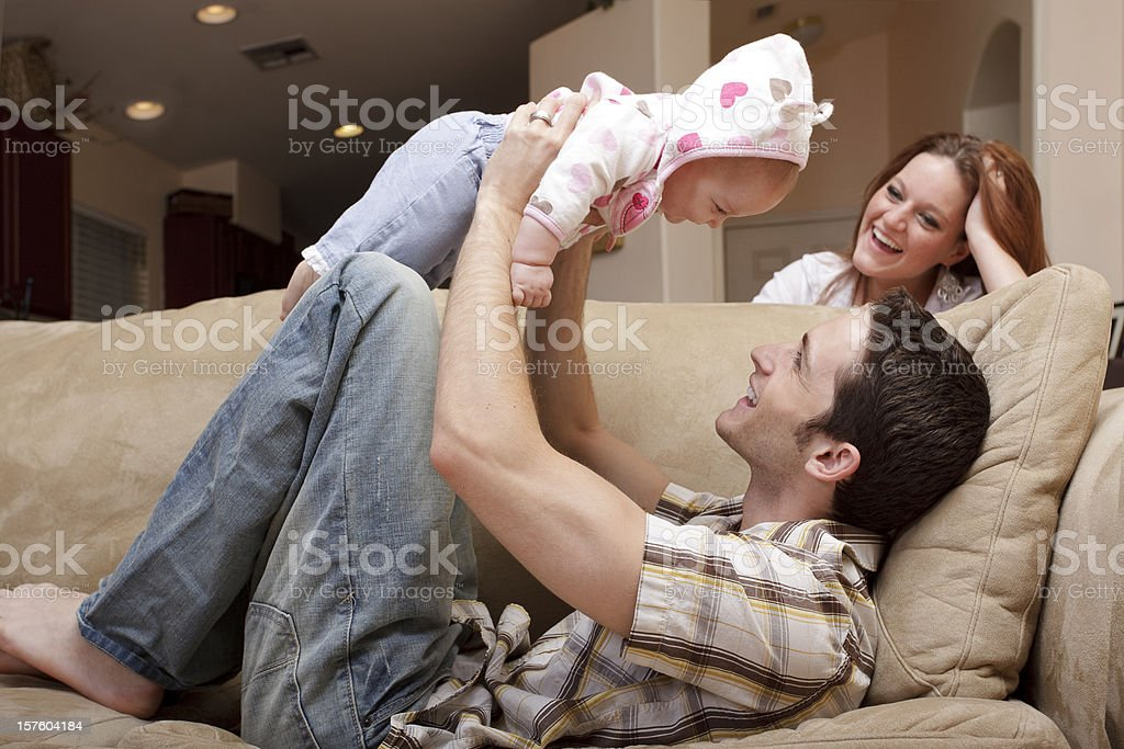 Family of Three Playing on Couch royalty-free stock photo