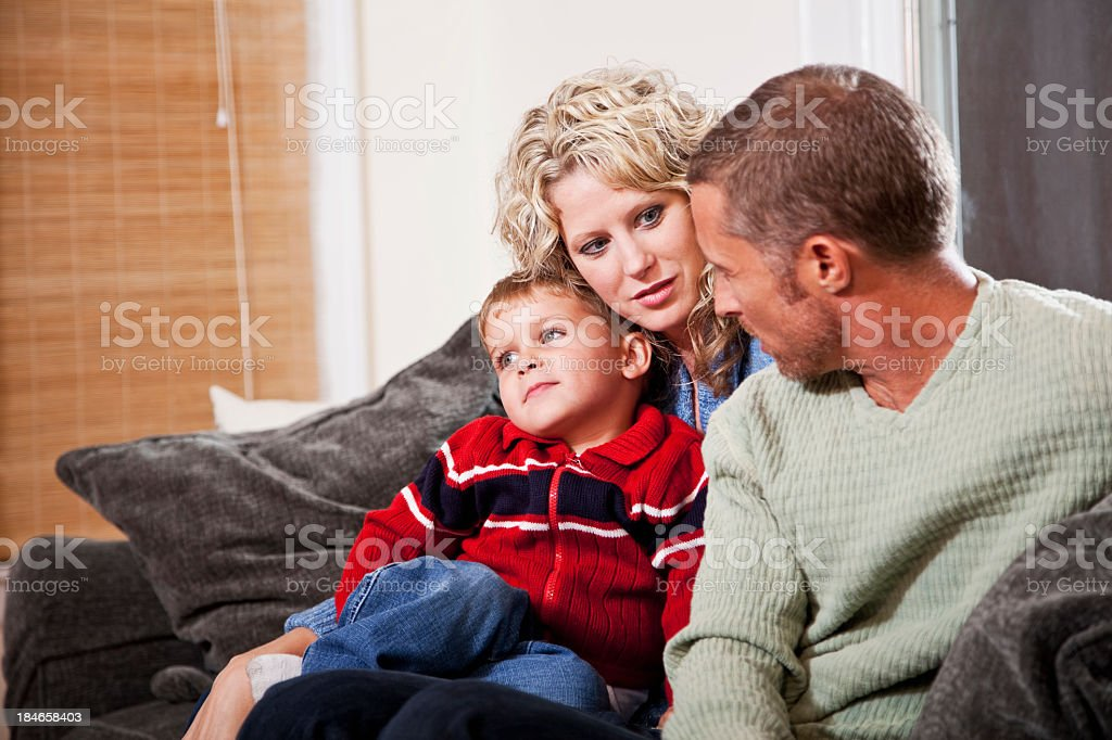 Family of three sitting together on sofa stock photo