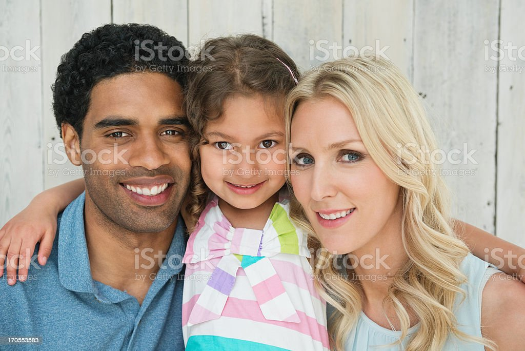 Family Of Three Smiling Against Wooden Wall royalty-free stock photo