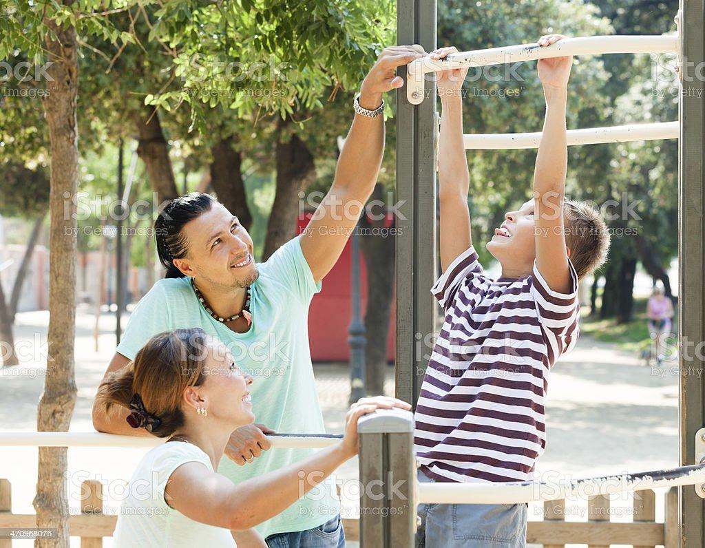 Family of three  training on chin-up bar stock photo