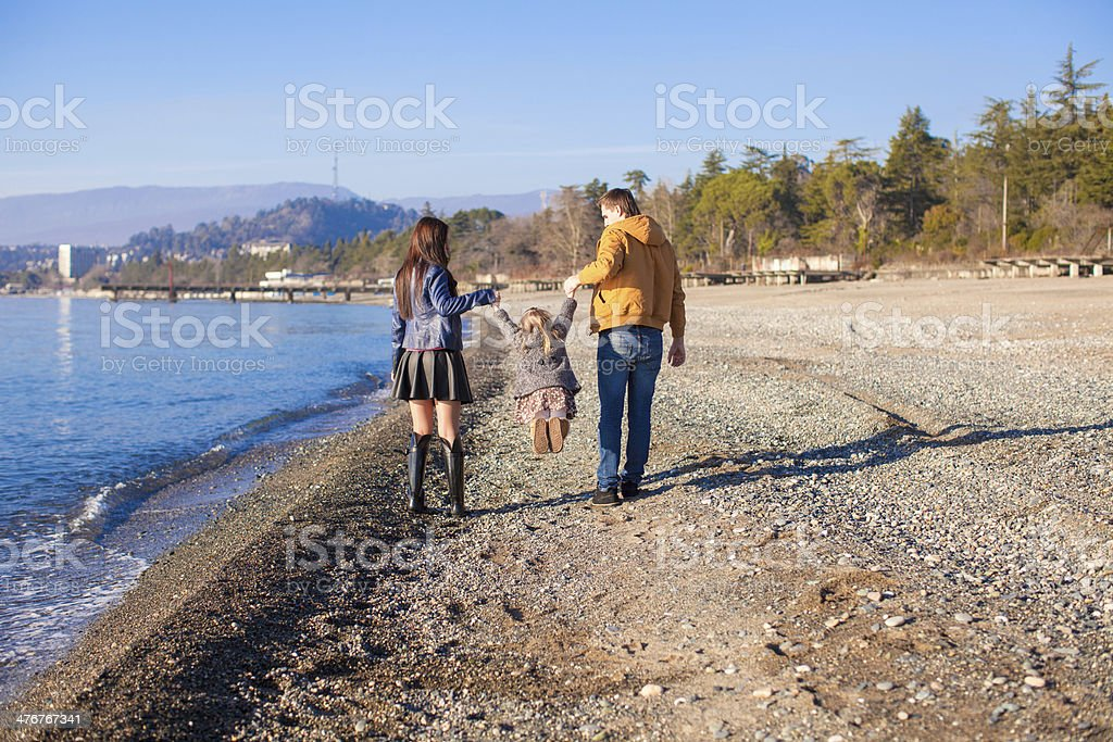 Family of three walking by the Black Sea stock photo