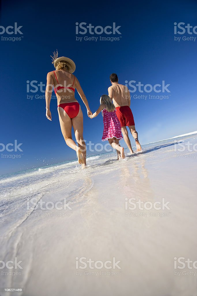 Family Of Three Walking On The Beach royalty-free stock photo