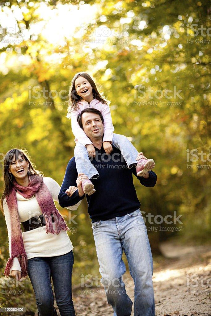 Family of Three Walking Through Autumn Woods royalty-free stock photo