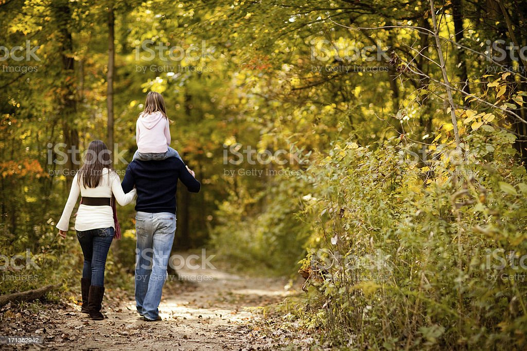 Family of Three Walking Through Autumn Woods, With Copy Space stock photo