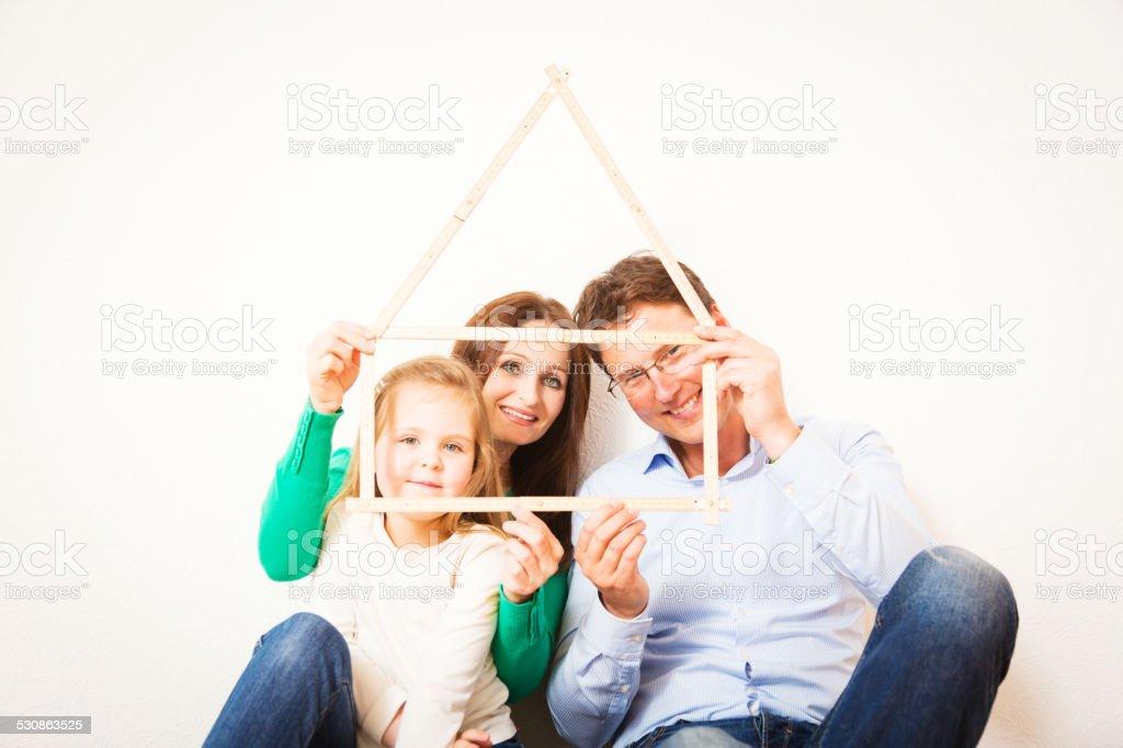 family of three with house shape stock photo
