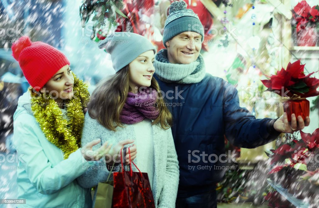 family of three with teenage girl choosing  floral decorations stock photo